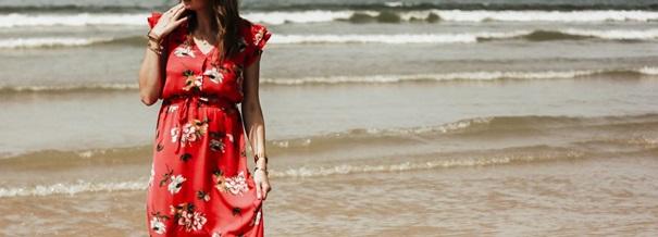 jeune femme en robe rouge sur la plage